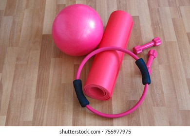 Pilates ball and circle, pink dumbbell on yoga mat, healthy life and sport concept, wooden background.
