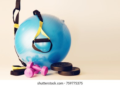 pilates ball with dumbbells and trx strings on white background and floor