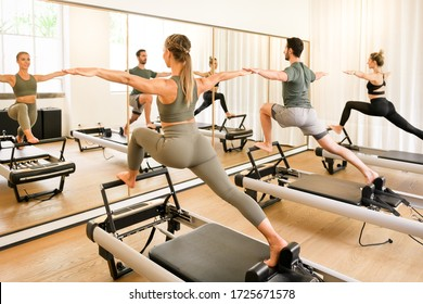 Pilates class of athletes doing a standing lunge exercise on reformer beds reflected in a wall mirror in a high key gym in a health and fitness concept