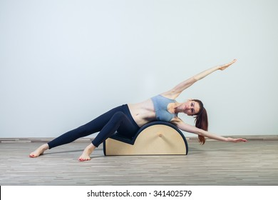 Pilates, fitness, sport, training and people concept -  woman doing  exercises on small barrel.