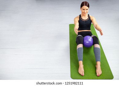Pilates, fitness, sport, yoga, training and people concept. Beautiful young woman in sportswear with big smile doing pilates and yoga exercises with purple ball between the legs in a gym.. Green mat.
