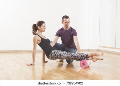 Pilates instructor coaching a beautiful woman using foam roller