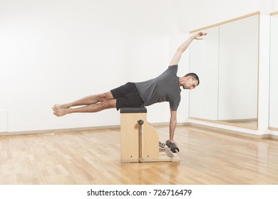 Pilates instructor performing fitness exercise on chairl equipment, at the gym indoor
