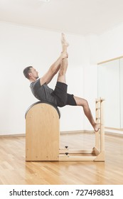 Pilates instructor performing fitness exercise on barrel equipment, at the gym indoor