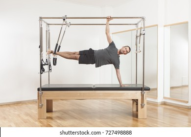 Pilates instructor performing fitness exercise on cadillac equipment, at the gym indoor