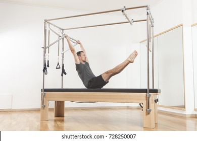 Pilates instructor performing fitness exercise on trapeze equipment, at the gym indoor