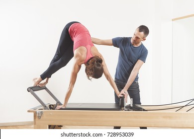 Pilates lesson on reformer, personal coaching young beautiful woman