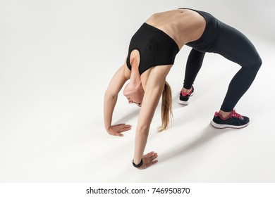 Pilates pose. Athletic woman doing hard exercising. Indoor shot, gray background
