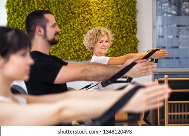 Pilates reformer elderly blond curly woman gym fitness teacher workout back and hands exercise on Pilates reformer device together with clients - Pilates, fitness, sport, training and people concept.