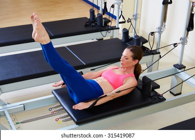 Pilates reformer woman hundred exercise workout at gym indoor