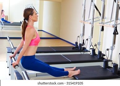 Pilates reformer woman tendon stretch exercise workout at gym indoor