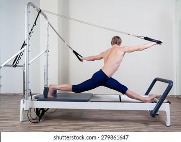Pilates reformer workout exercises man at gym indoor