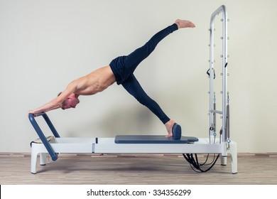 Pilates reformer workout exercises man  at gym indoor.