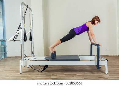 Pilates reformer workout exercises woman brunette at gym indoor
