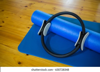 Pilates ring and exercise mat kept on wooden floor in fitness center