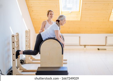 Pilates studio machine for fitness workouts in gym. Side view senior woman workout with fitness instructor performing pilates exercise, training on barrel equipment inside modern studio..