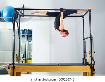 Pilates woman in cadillac walk over reformer upside down exercise at gym