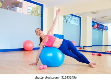 Pilates woman fitball side bend exercise workout at gym indoor