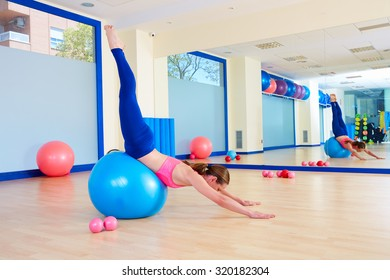 Pilates woman fitball swan dive exercise workout at gym indoor