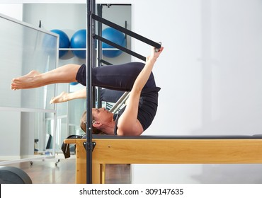 Pilates woman in reformer roll over exercise at gym indoor