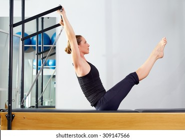 Pilates woman in reformer teaser exercise at gym indoor