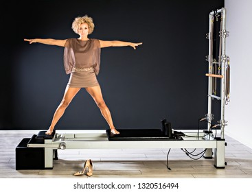 Pilates woman in reformer tower exercise at gym in short elegant dress