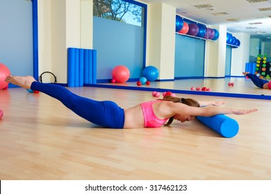 Pilates woman roller swan dive roll exercise workout at gym indoor