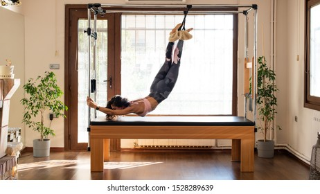Pilates Woman stretching on pilates cadillac. Young female pilates instructor exercising. Concept for pilates.