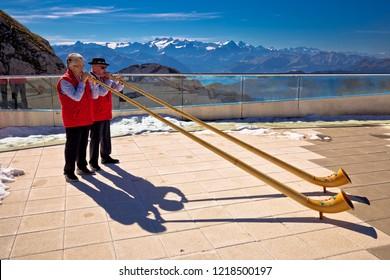 Pilatus, Switzerland, September 25 2018: Traditional Swiss Alphorn players on Pilatus mountain peak playing horn for tourist. Alpine peaks background. Alphorn is long wooden musical instrument.