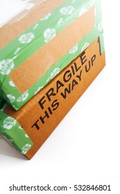 A pile of 2 wrapped up parcels on a white background, with blank labels and green recycled parcel tape