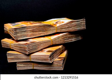 Pile of 50 real euro notes 50-euro banknotes under rubber band, isolated on black background. About 2500 euros worth