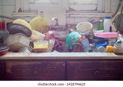 Pile of abandoned dirty utensils in a kitchen washbasin