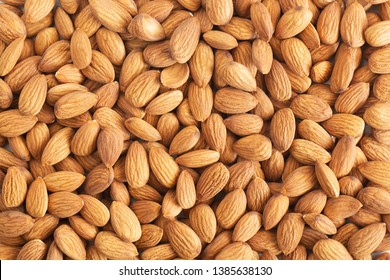 Pile of almond nuts on wood table,Top view.