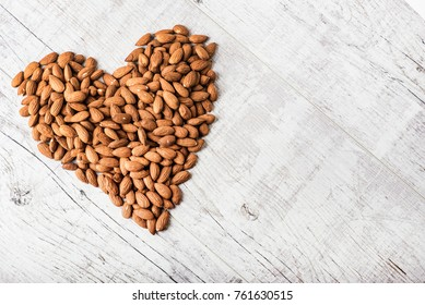 Pile of almonds in heart shape. Fresh nuts.