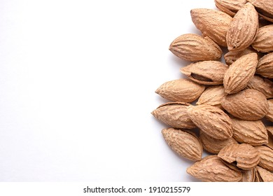A pile of almonds on a white background. Salted fresh nuts in the shell lie in a handful isolated from the background