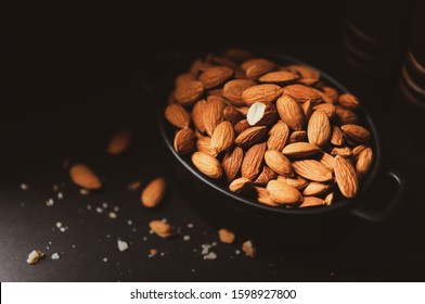 A Pile of Almonds in a Small Bowl on a Black Background in a Dark Moody Setting