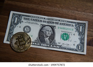 Pile of American one dollar cash. Next to it are several gold bitcoin digital cryptocurrency coins. Bank image and photo background.