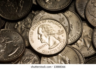 Pile of American Quarter Dollar Coins. Lighting & focus centered on middle coin.