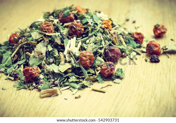 Pile of assorted natural medical dried herb leaves and fruits on wooden surface. Herbaceous plant.