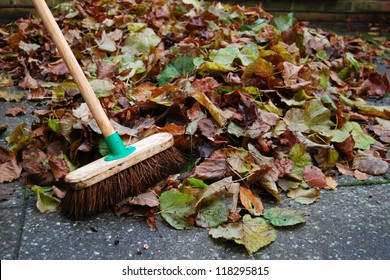 Pile of autumn leaves on backyard patio and sweeping brush