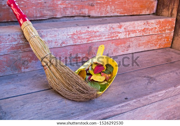 A pile of autumn red and yellow leaves, swept with a broom of sorghum with a red handle in a yellow scoop, lying at the entrance to the village house on the  porch made of wooden peeling brown boards