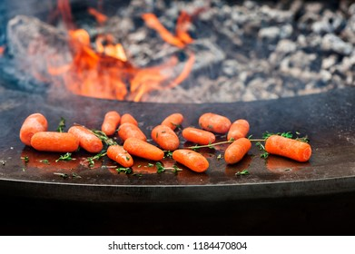 Pile of baby carrots with rosemary ready for grilling