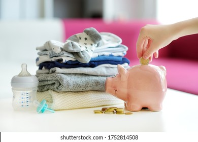 A pile of baby clothes, piggy bank, pacifier and a feeding bottle. Parenting expenses concept. Working out a baby budget. Saving money when planning for a newborn. Budgeting for a new baby.