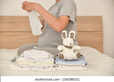 Pile of baby clothes and pregnant woman on a bed