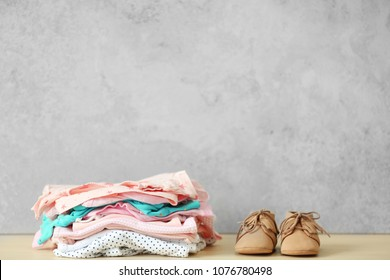 Pile of baby clothes and shoes on table