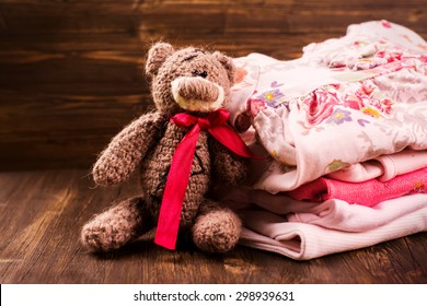 Pile of baby clothes with a teddy bear. Baby shower greeting card. It's a girl. Selective focus. Vintage style. Toned image