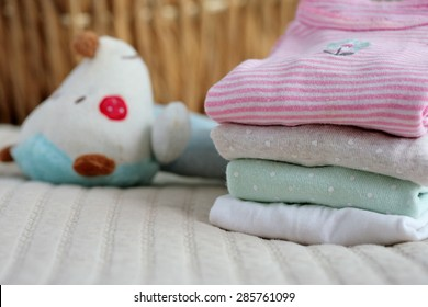 Pile of baby clothes and a toy