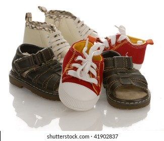 pile of baby or infant shoes with reflection on white background