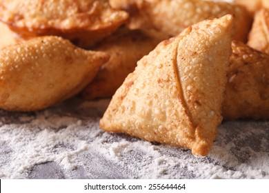 A pile of baking samosas macro on the table with flour. horizontal