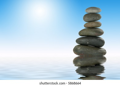 Pile of Balanced Stones in Zen-like Setting with Reflection Representing Meditation.